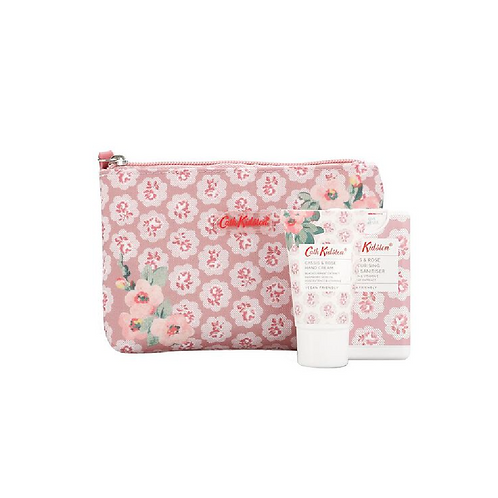 Hand cream and sanitiser in front of a floral makeup bag