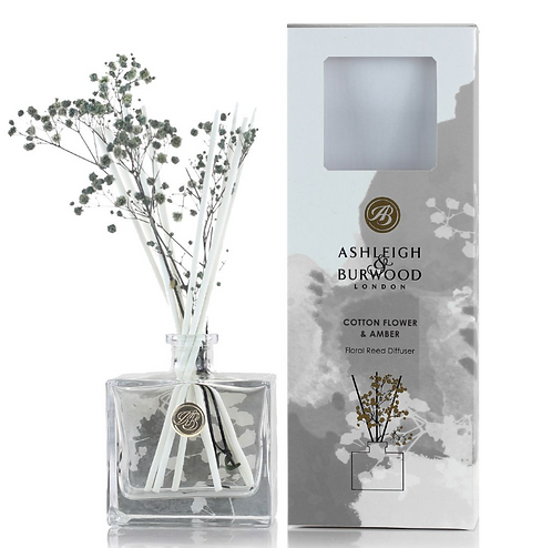 Clear glass bottle with floral reeds and grey and white box