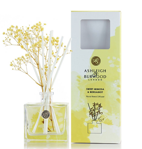 Clear glass bottle with floral reeds and yellow and white box
