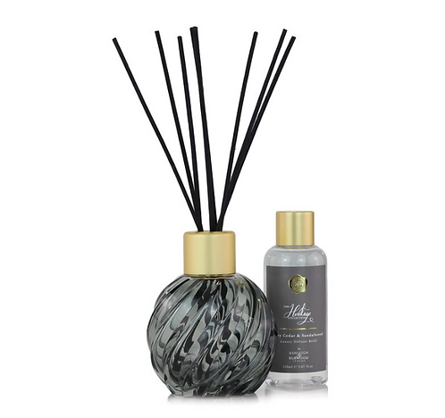 Grey diffuser vessel with sticks and bottle