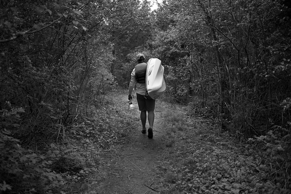 Author Ben Duchesney walks through the woods with a kayak.