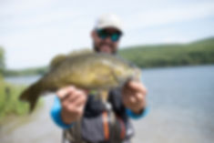 Author Ben Duchesney holds up a big smallmouth bass caught in Vermont.