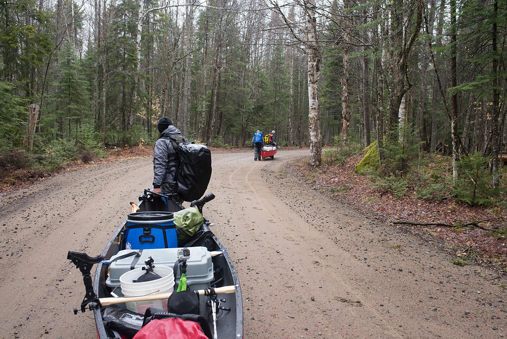 Paddlers walk their gear and canoes through the woods in the Adirondacks.
