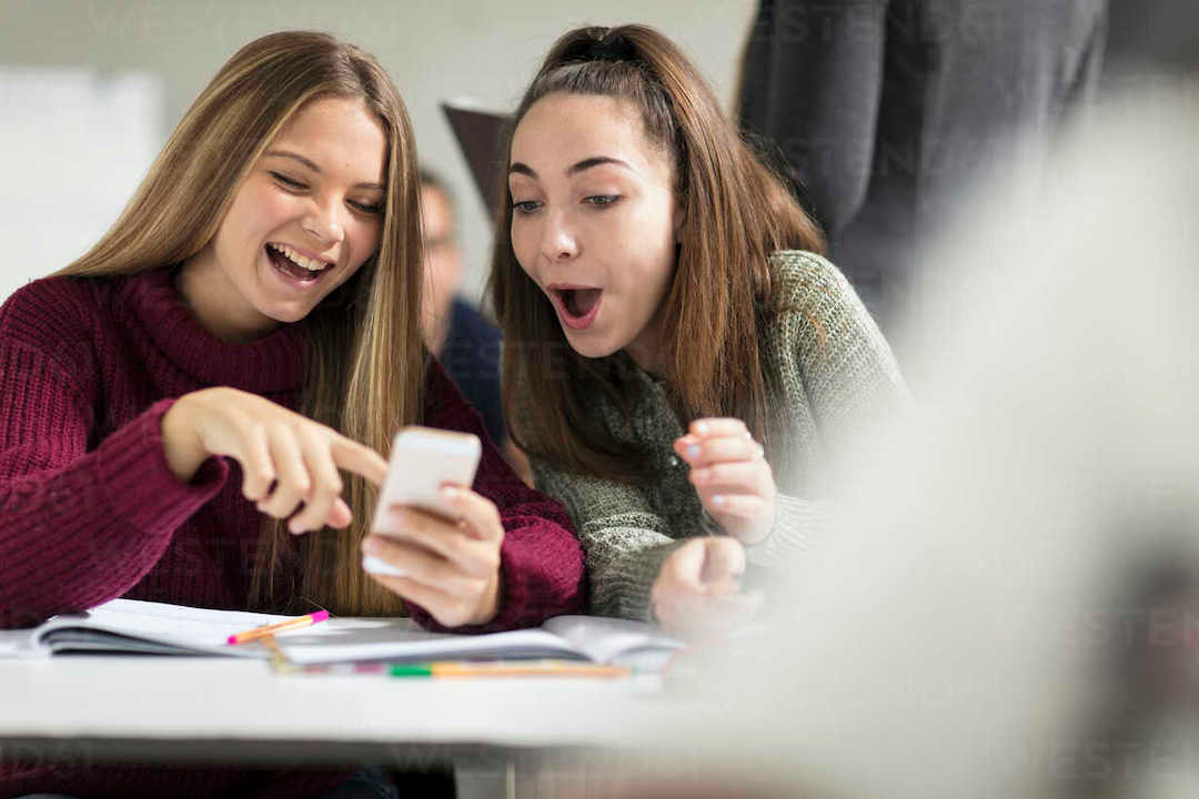 happy-teenage-girls-in-class-looking-at-