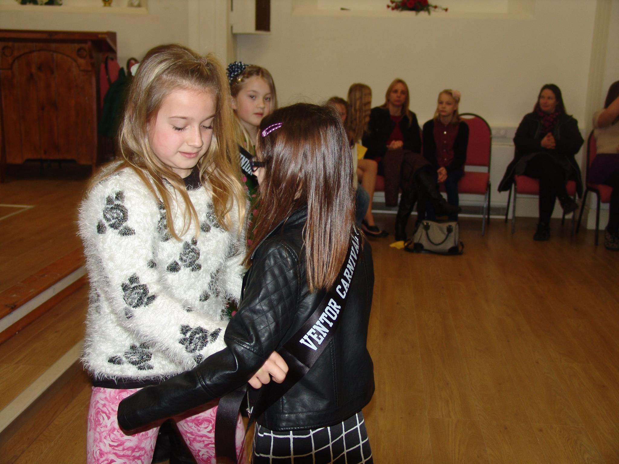 Retiring Junior Queen awarding new Junior Queen sash.jpg