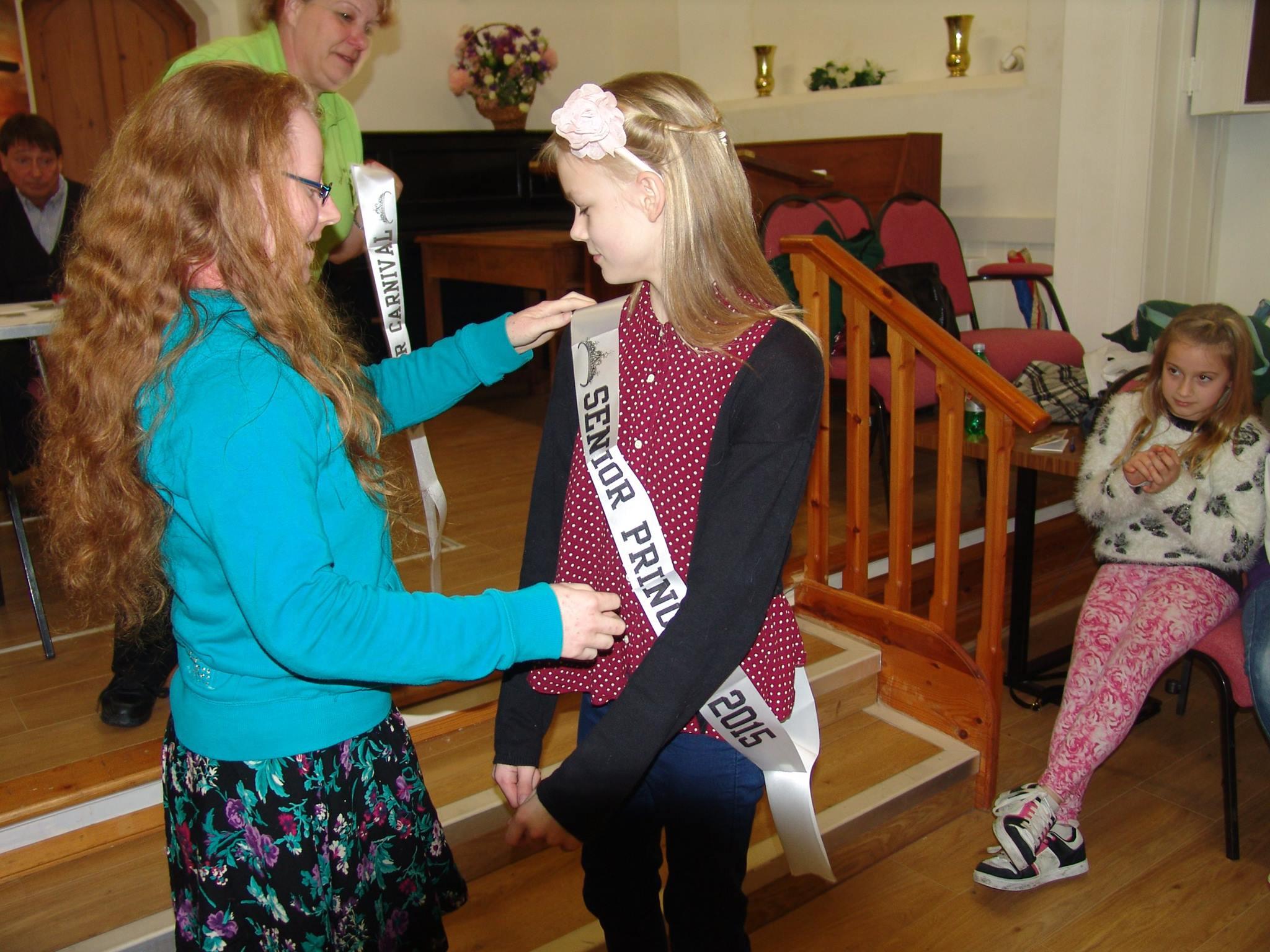 Senior Queen awarding the new princess sash