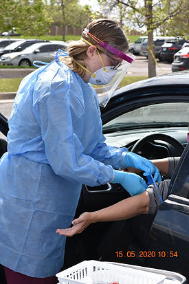 Woman wearing personal protective equipment administering a COVID-19 antibody test at a drive-up COVID testing center