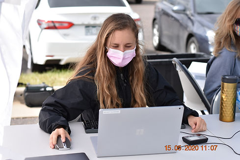 Woman wearing a mask, working on a laptop at a COVID-19 drive-thru testing center