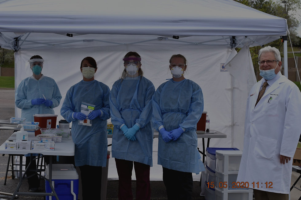 Medical professionals in masks ready to administer drive-up COVID-19 tests