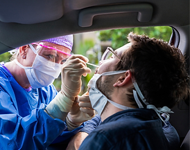 Medical professional administering a COVID-19 nasal swab test to a man in a car at a COVID-19 drive-thru testing center