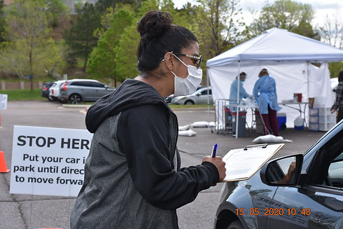 Woman in sweatshirt wearing mask, holding a clipboard while talking to someone in a car at a COVID-19 drive-up testing center in Colorado