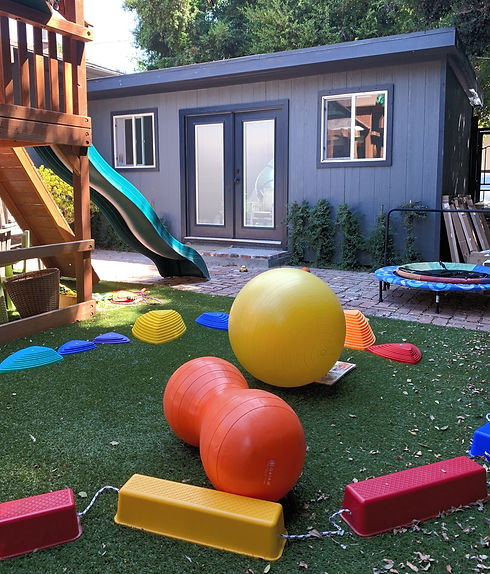 Willowcrest outdoor area with colorful balls, steps, and play equipment.
