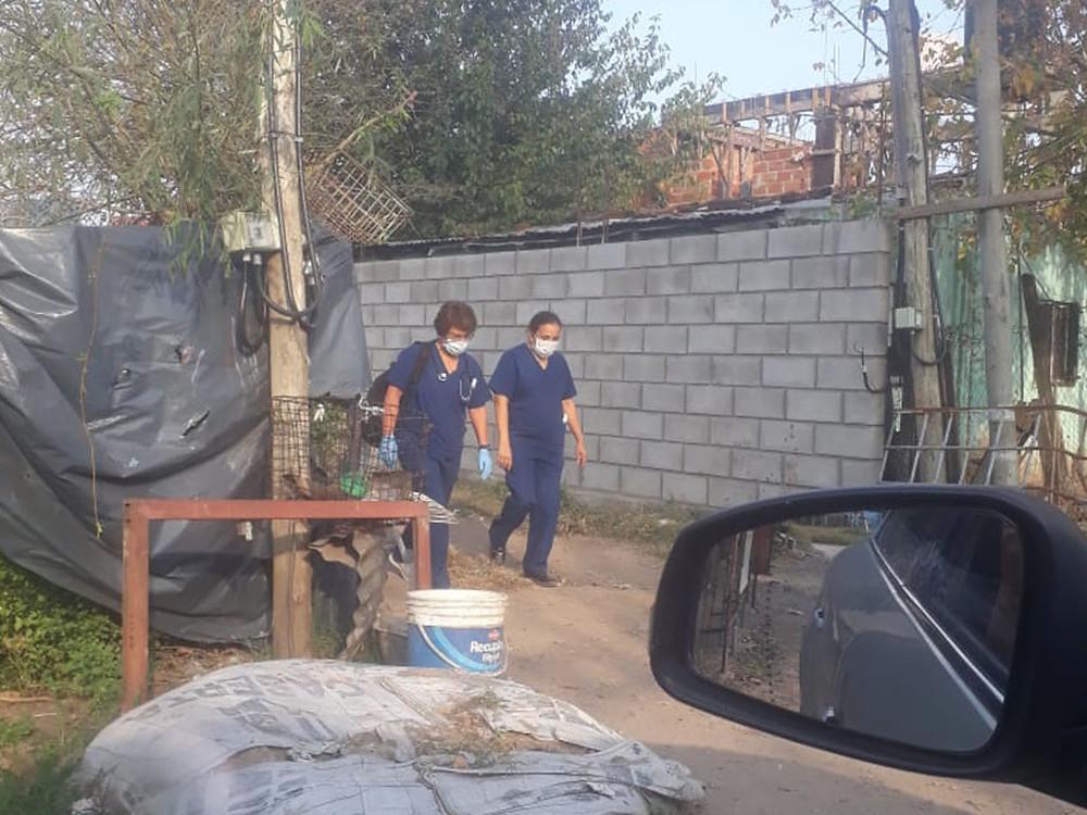 Dos enfermeras del Hospice Buen Samaritano caminan bajo el sol por un barrio