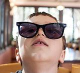 boy wearing sunglasses sitting on brown chair_edited.jpg