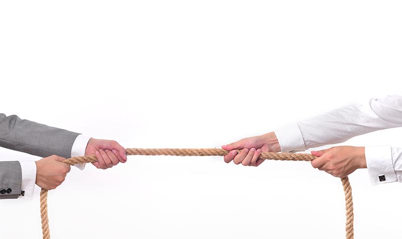 Imagem onde uma corda é puxada em direções opostas por duas pessoas de roupa social.