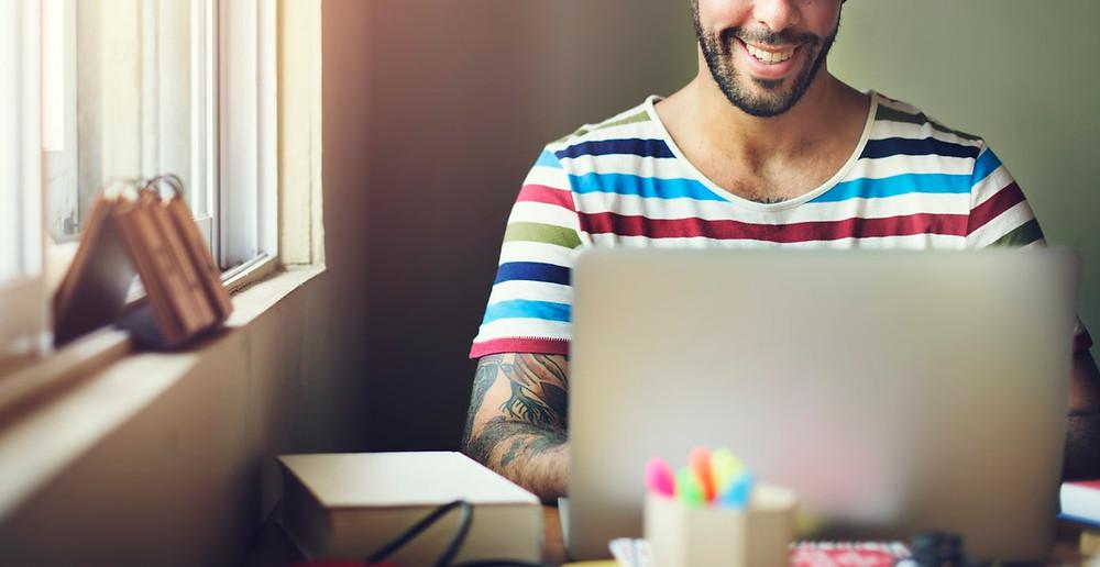 Homem sorrindo para tela do computador.