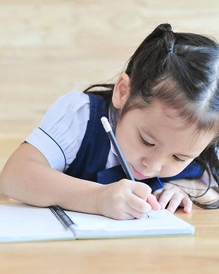 little asian school girl writing noteboo