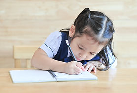 little asian school girl writing noteboo