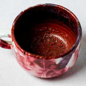 Red acrylic paint in a cup
