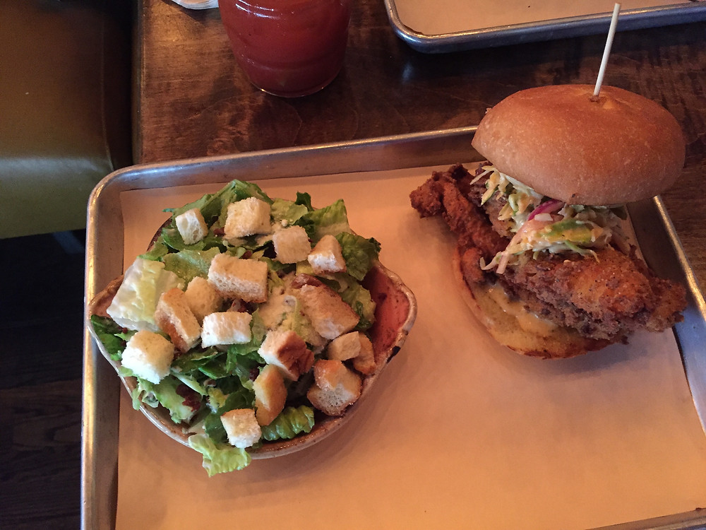 Fried chicken sandwich and caesar salad from Pogue Mahone in Toronto, Ontario