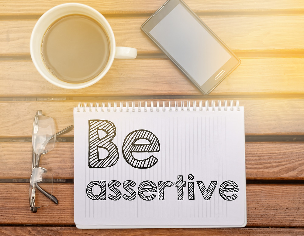 Be assertive sign on a notebook