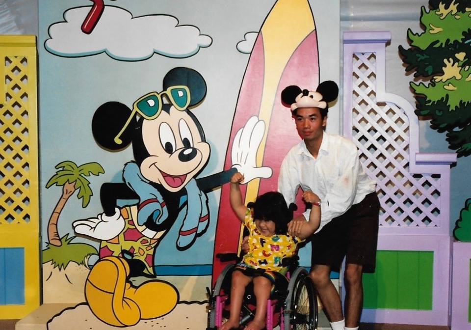 A photo in front of a Mickey Mouse image in Disney World