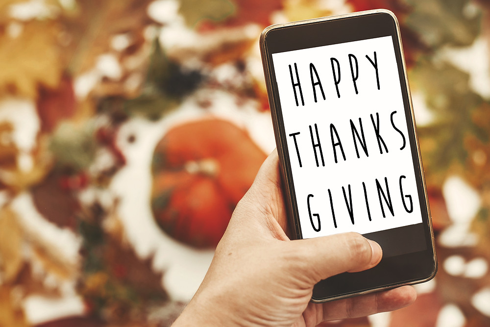 Happy Thanksgiving is typed on a cell phone in front of a background of pumpkins and leaves.