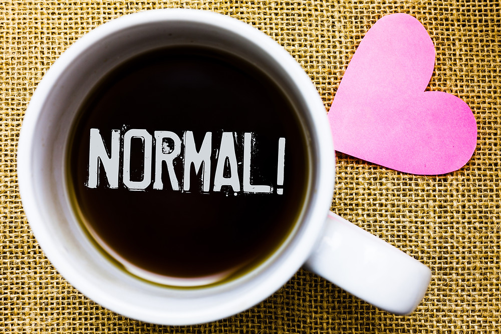 A photo of a mug with the word normal with an exclamation mark with a pink heart beside it.