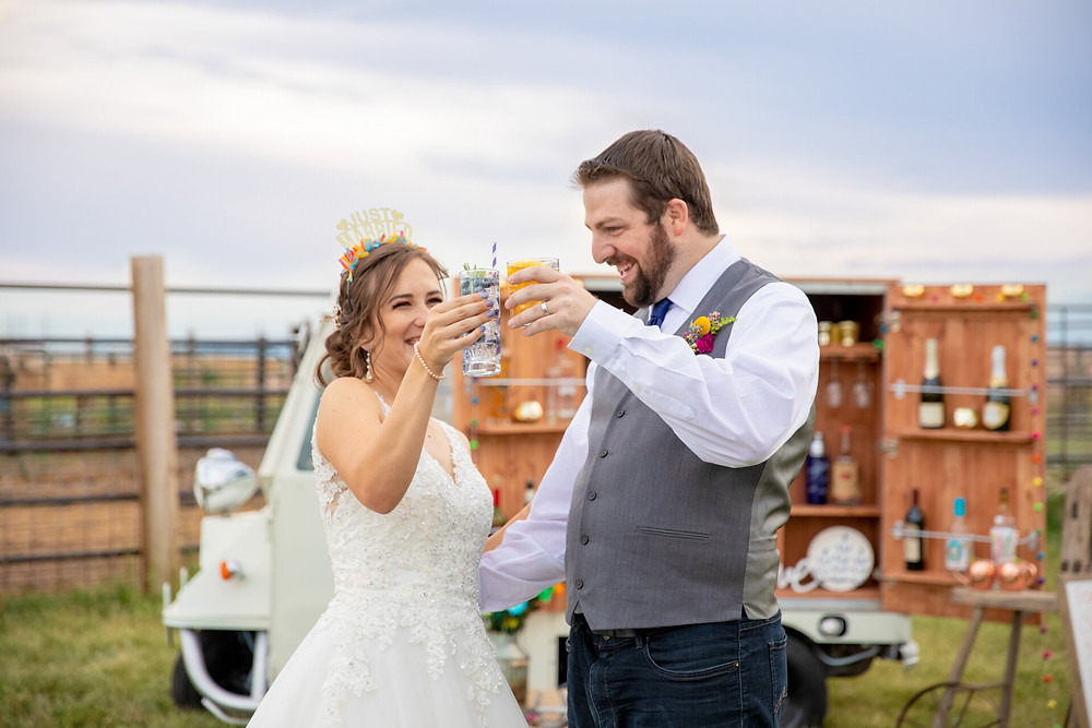 Couple having drinks at wedding with wandering wagon bar, real glassware