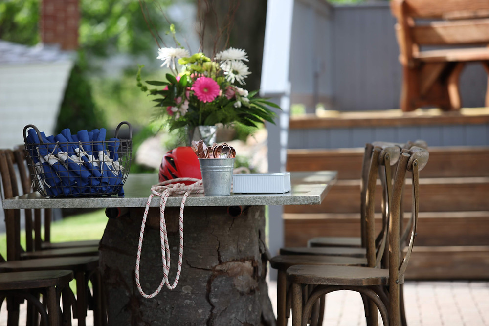 tree trunk table with a piece of marble surrounded by eight cross back chairs, flowers, climbing gear, rock climbing wedding, Colorado Wedding Planner