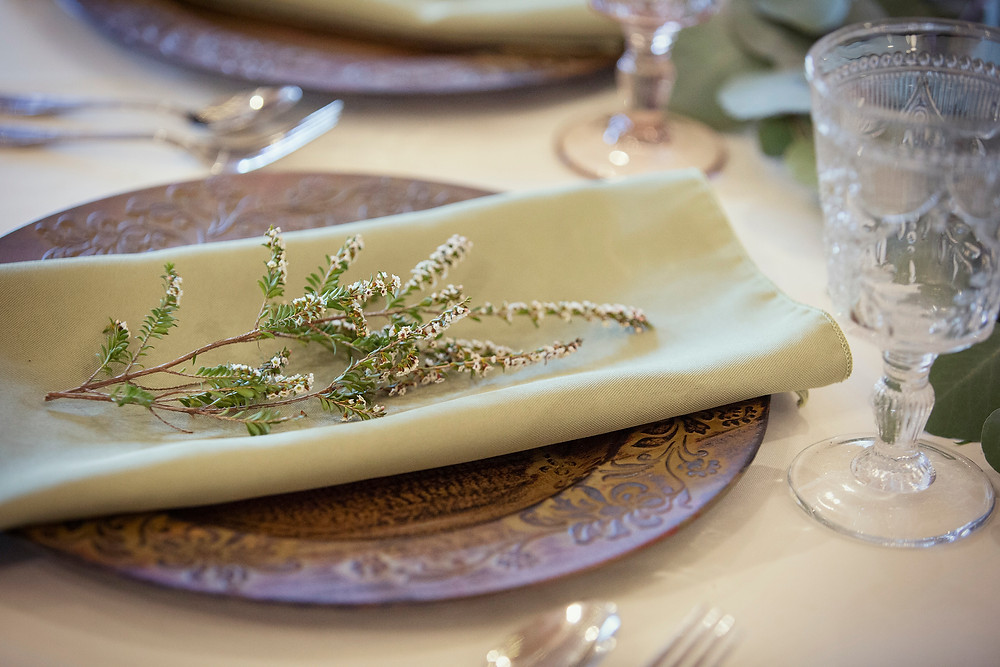 wedding table setting with green napkin on charger and limonium sprig