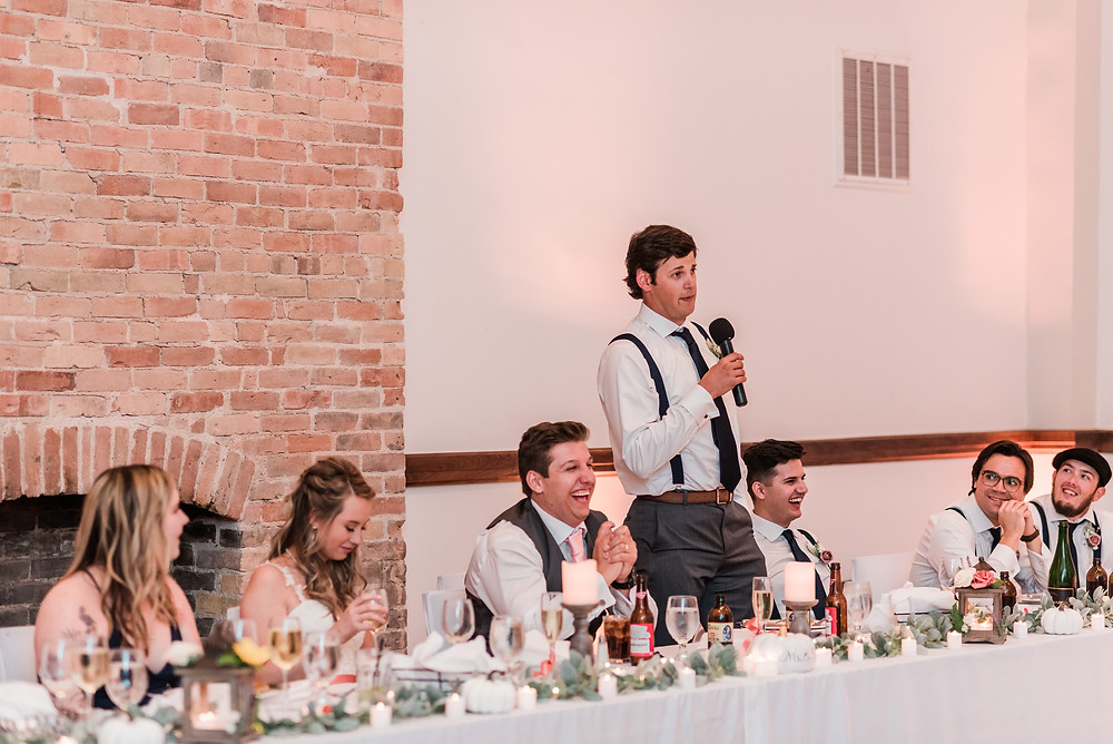Head table with fireplace in Colorado with best man giving speech.