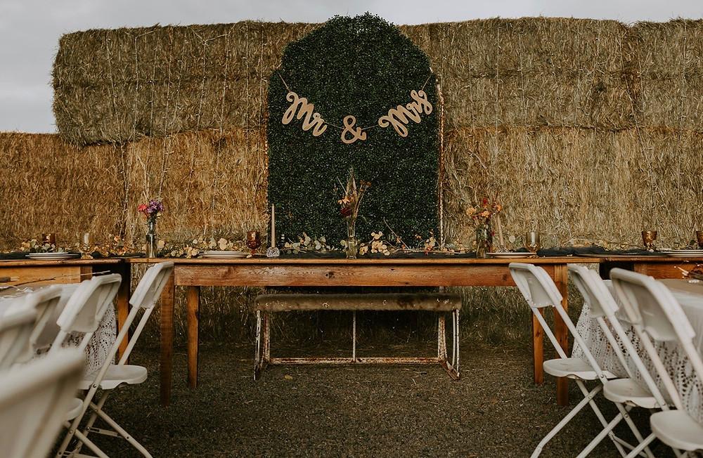 hay bail backdrop for head table with vintage decor Colorado wedding