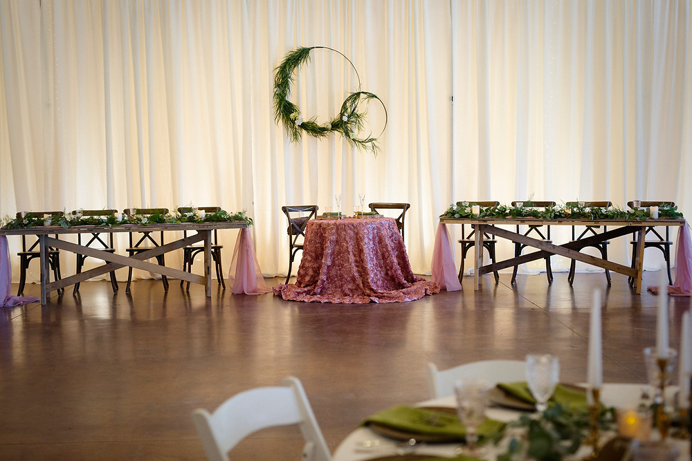 Sweetheart table with tables for wedding party, pink linen, greenery, x-back chairs, full drape