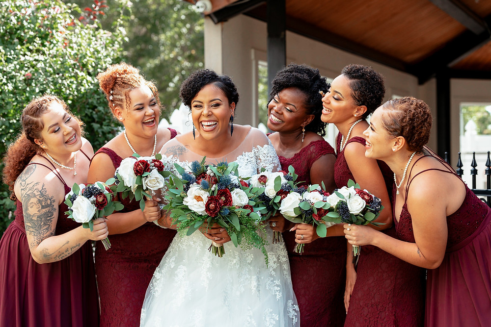 Women of color bridesmaids holding environmentally friendly faux floral bouqets from compass rose floral
