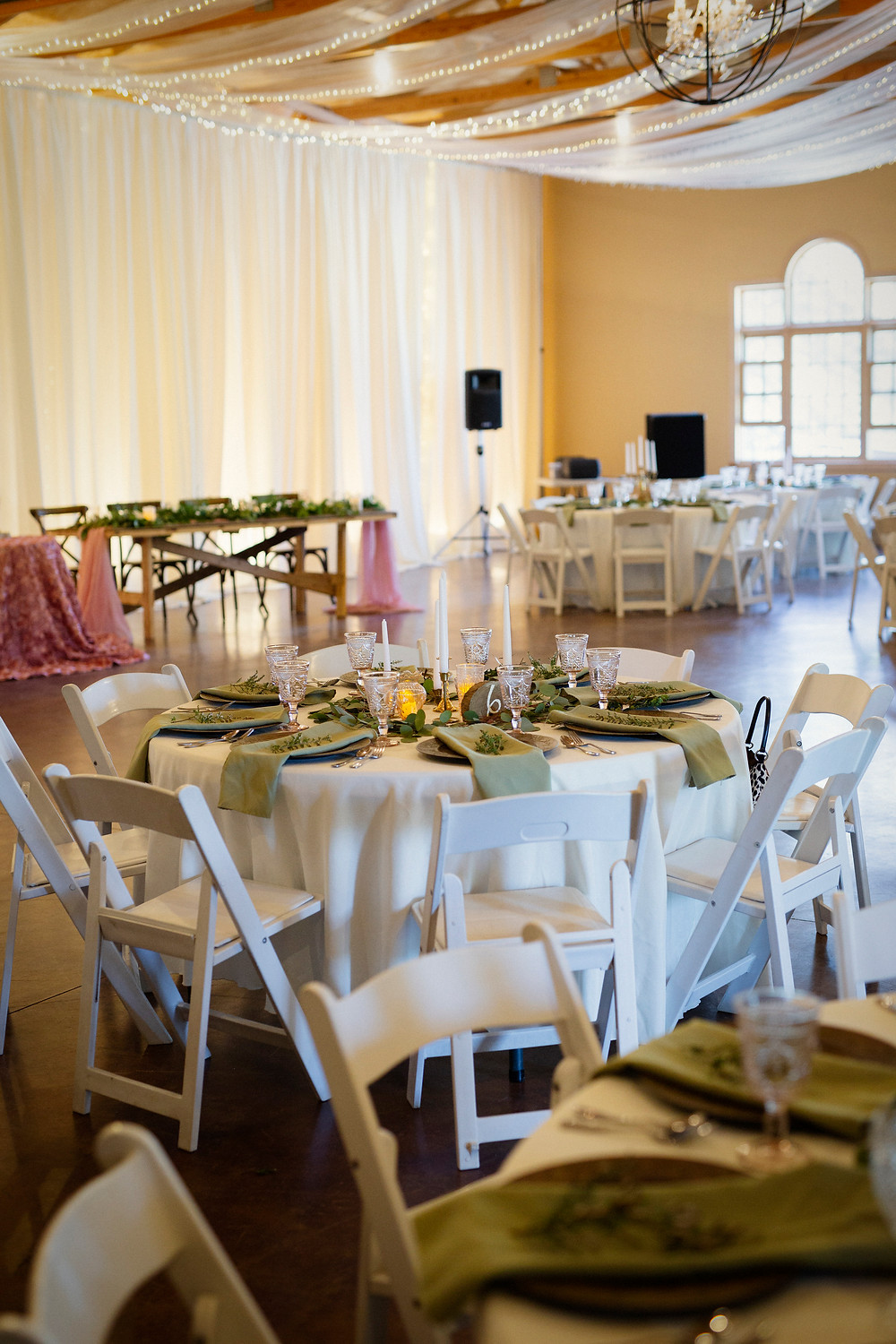 Round wedding tables with white linens, candles, green napkins, vintage barn wedding