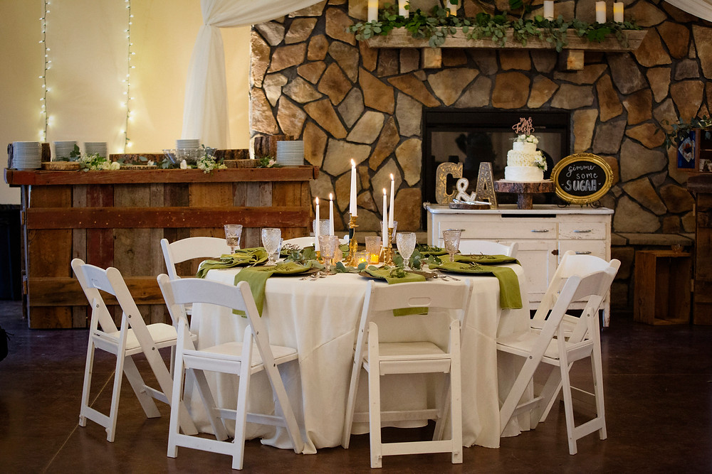 White padded resin folding chairs at round wedding table
