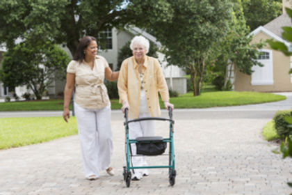 caregiver-with-senior-using-walker-outsi