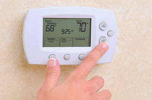 Hand pressing buttons on thermostat