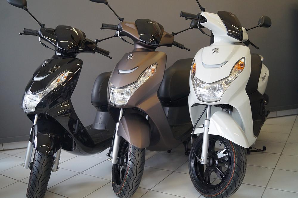 Tre mopeder, en sort til høyre, en brun i midten, og en hvit til venstre