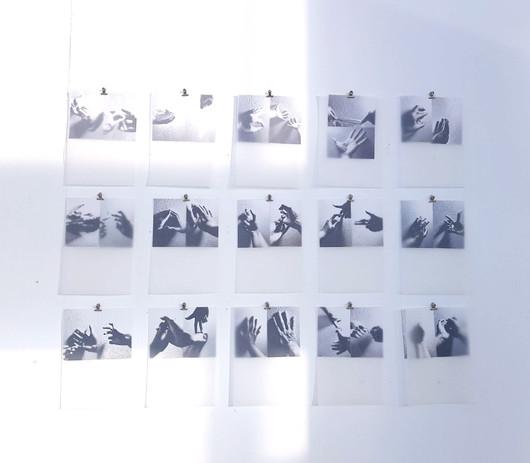 Vue d'accrochage, photographies imprimées sur papier; papier calque. Mains.