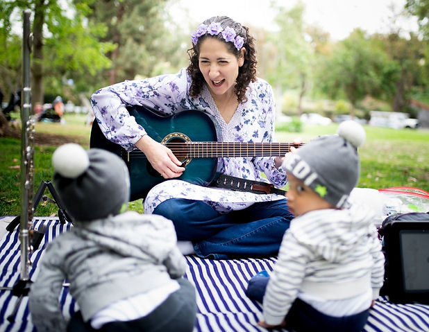Kira Rappaport with guitar singing with babies and todlers