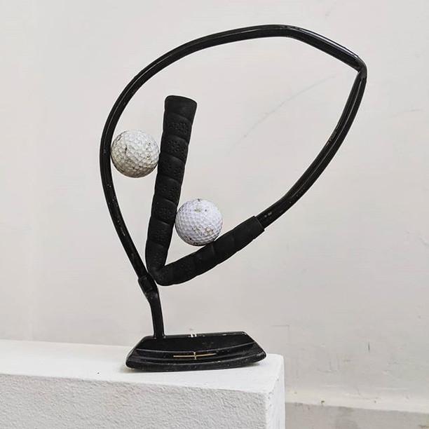A Golf Putter Holding 2 Golf Balls