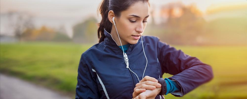 Mulher com roupas de academia e fones de ouvido olhando o relógio.