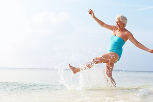 Senior Woman Splashing In Sea On Beach H