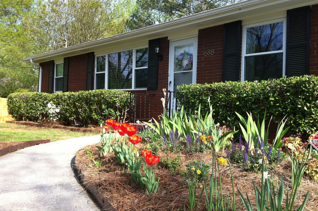 The exterior of Kosta at Smyrna resembles a beautiful family home. Its entryway features a paved path to the front door that's lined with bushes and flowers.