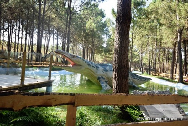 Amphibian Dinosaur Sculpture in a pond among pine trees