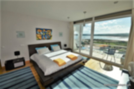 Luxury master bedroom with frontal French doors, looking out to breathtaking views