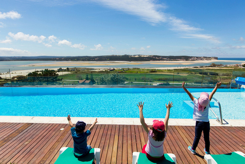 Kids enjoy the heated and fenced pool in the holiday villa Casa do Lago