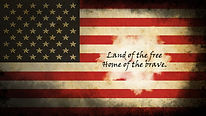 Distressed American Flag with Land of the free Home of the brave written across the front.